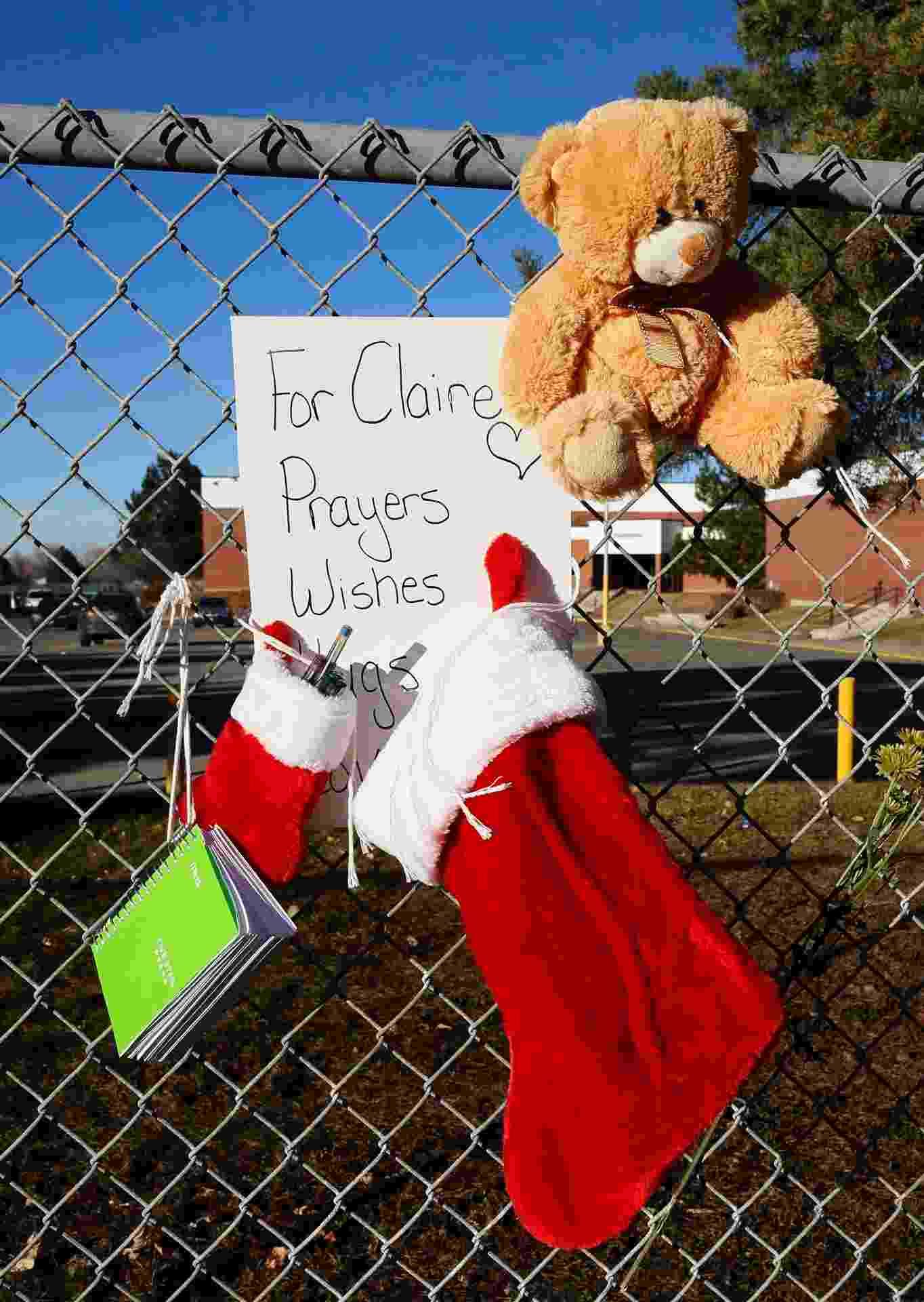 15.dez.2013 - Enfeites de Natal e um recado pedindo orações para Claire Davis são pendurados em cerca no colégio Arapahoe, no subúrbio de Denver, Colorado (EUA). Davis, 17, levou um tiro de um colega armado que invadiu a escola - Rick Wilking/Reuters