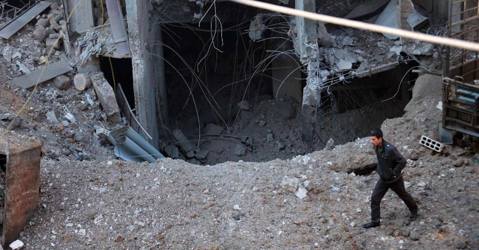 15.dez.2013 - Homem caminha por escombros de um prédio na cidade de Damasco, na Síria. Ativistas acreditam que o edifício tenha sido atacado por forças leais a Bashar al-Assad, presidente do país