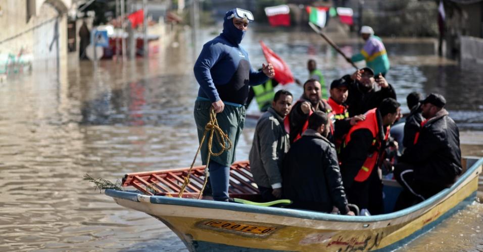 15.dez.2013 - Membros da defesa civil palestina usam barco para prestar socorro a moradores de um bairro inundado na cidade de Gaza. Cerca de 5.000 pessoas foram retiradas do local