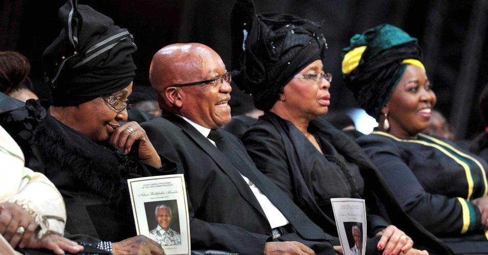 15.dez.2013 - O presidente da África do Sul, Jacob Zuma, acompanha funeral de Nelson Mandela. À esquerda, está Winnie Mandela Madikizela, ex-mulher do ex-presidente sul-africano, e à direita está Graça Machel, viúva de Mandela