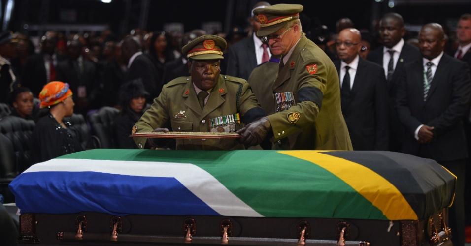 15.dez.2013 - Oficiais do Exército deixam um quadro sobre o caixão do ex-presidente sul-africano Nelson Mandela durante seu funeral em Qunu