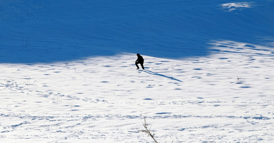 15.dez.2013 - Palestino caminha sobre monte coberto pela neve em Nablus, na Cisjordânia. Milhares de pessoas ficaram sem eletricidade após uma tempestade de neve que atingiu o Oriente Médio por três dias
