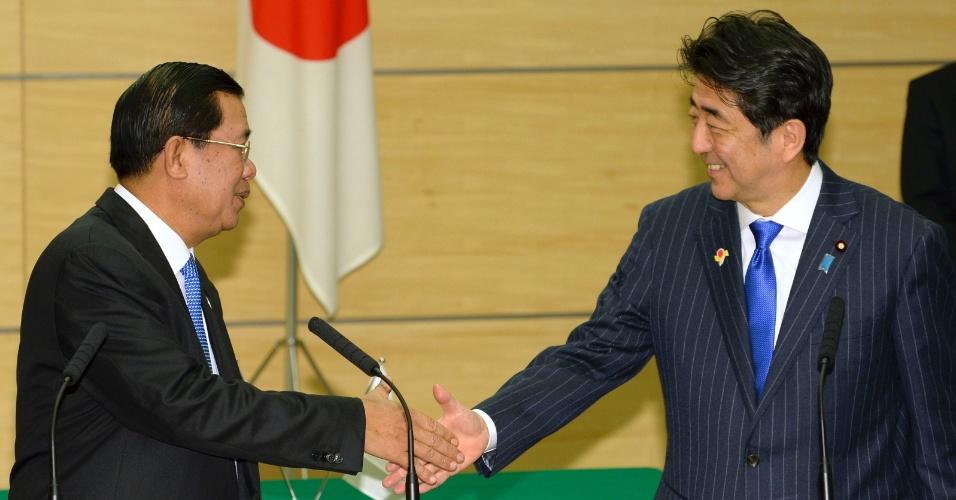 15.dez.2013 - Samdech Hun Sem, primeiro-ministro do Camboja, cumprimenta Shinzo Abe, primeiro-ministro do Japão, durante um encontro na residência oficial do governo japonês em Tóquio. Os chefes dos dois países anunciaram uma série de acordos comerciais