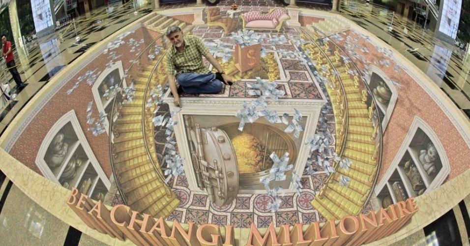 10.mai.2012 - O artista estadunidense posa para foto sobre pintura feita em terminal do aeroporto Changi, em Cingapura
