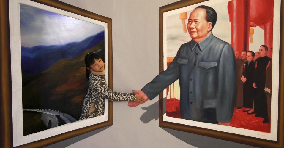 16.dez.2013 - Garota chinesa interage com imagem em 3D do ex-líder comunista e revolucionário chinês Mao Tsé-Tung (morto em 1976), durante exposição em Binzhou, por ocasião do 120º aniversário de nascimento de Mao, celebrado no próximo dia 26