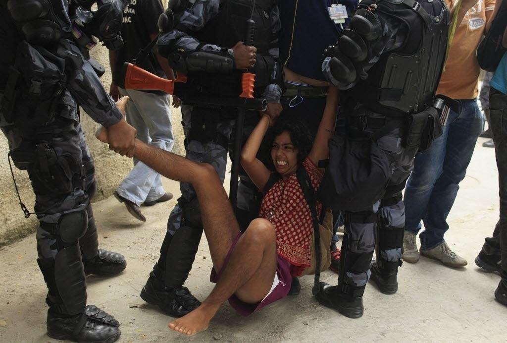 16.dez.2013 - Policiais dos Batalhões de Choque e de São Cristóvão realizam reintegração de posse de prédio vizinho ao antigo Museu do Índio, ao lado do estádio do Maracanã, zona norte do Rio. Os mais de 20 manifestantes detidos serão autuados por resistência, informou a polícia