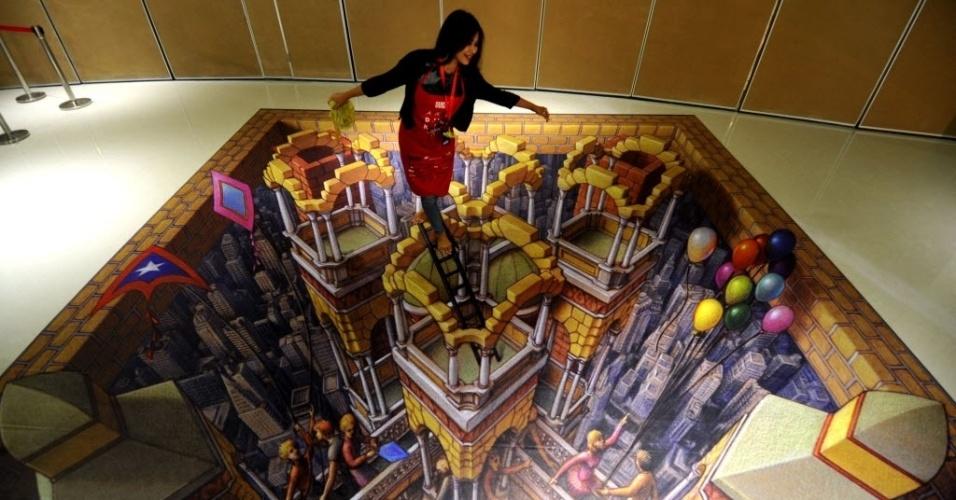 16.dez.2013 - Visitantes posam sobre pintura criada pelo artista estadunidense Kurt Wenner, durante a exibição Artphoria 2013, no Centro Ciputra Artpenuer, em Jacarta, na Indonésia. As pinturas com efeitos 3D, aliadas às poses e encenações das pessoas, criam ilusão de realidade, dando a sensação de altura e vertigem. A exposição Artphoria 2013 permanecerá no local até 26 de janeiro de 2014