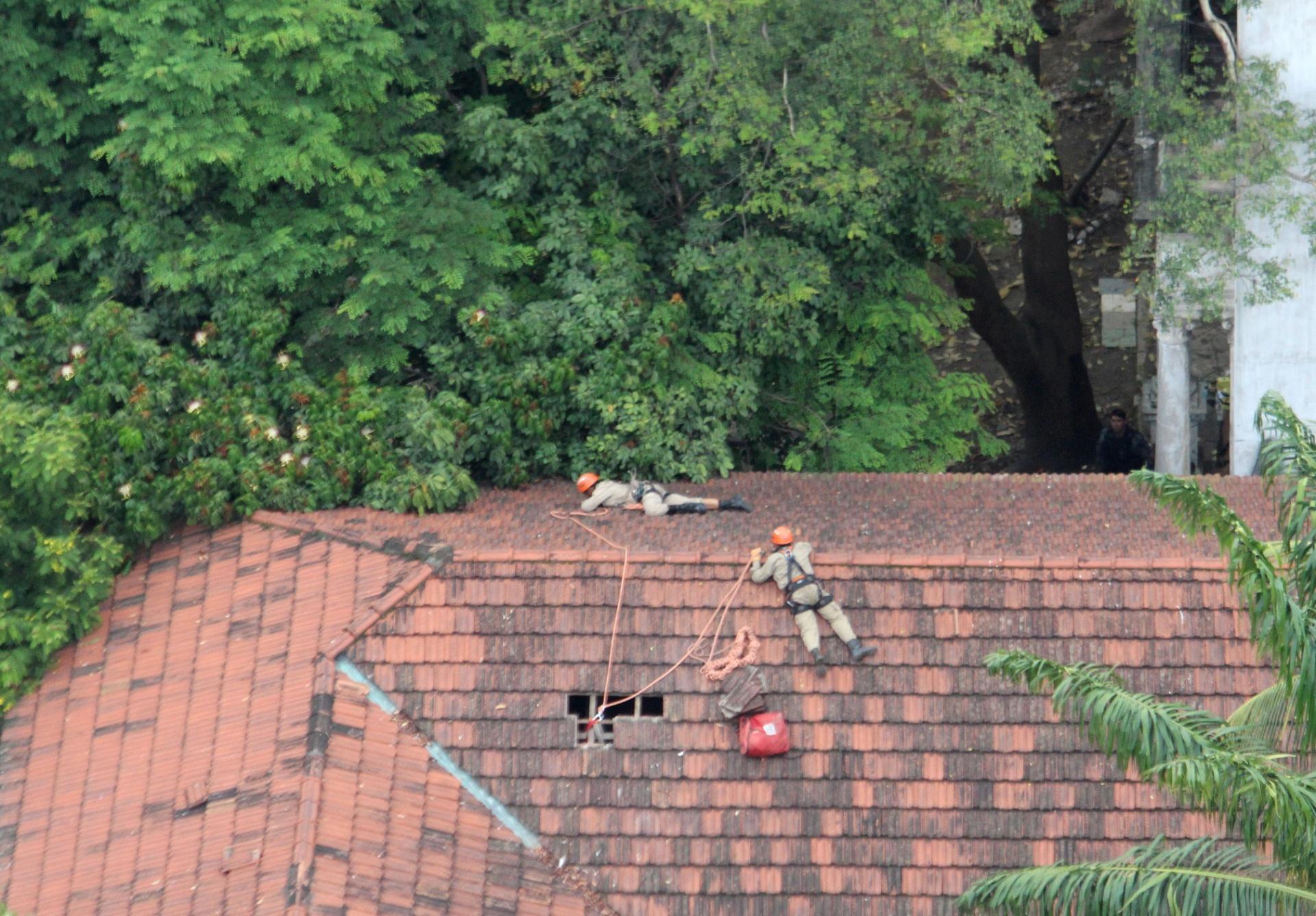 17.dez.2013 - Bombeiros sobem em telhado de prédio para tentar retirar o índio Urutau José Guajajara de uma árvore no terreno do antigo Museu do Índio, no Complexo do Maracanã, zona norte do Rio de Janeiro