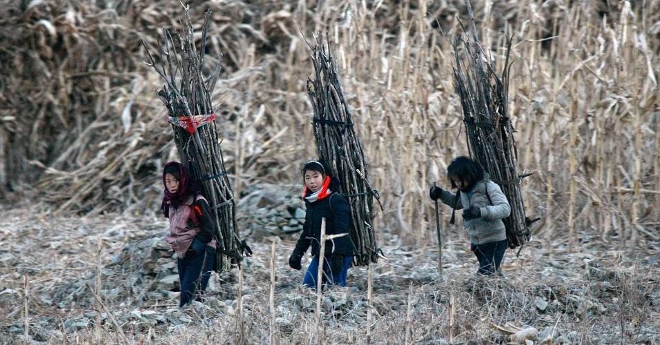 17.dez.2013 - Crianças carregam lenha nas costas às margens do rio Yalu, em Sinuji (perto da cidade fronteiriça de Dandong), na Coreia do Norte
