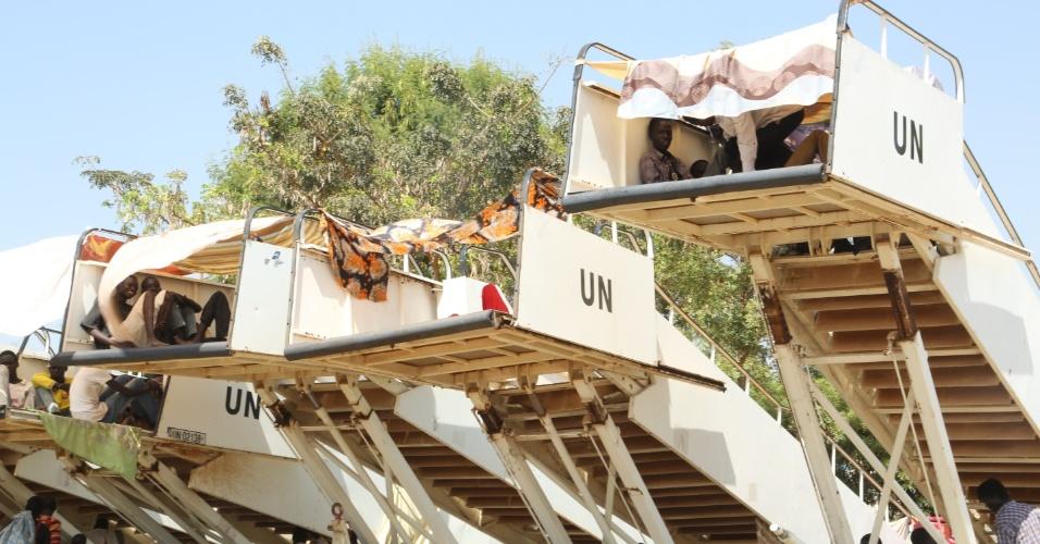 17.dez.2013 - Deslocados internos se abrigam do sol em escadas de embarque de aeronaves, nesta terça-feira (17), em uma instalação da ONU em Juba, no Sudão. Ao menos 66 soldados morreram nos últimos dois dias durante batalha contra grupos rebeldes