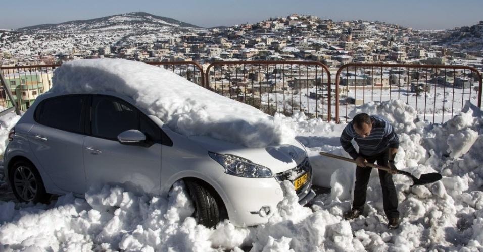 17.dez.2013 - Homem retira neve em volta de um veículo, na vila drusa de Beit Jann, no norte de Israel
