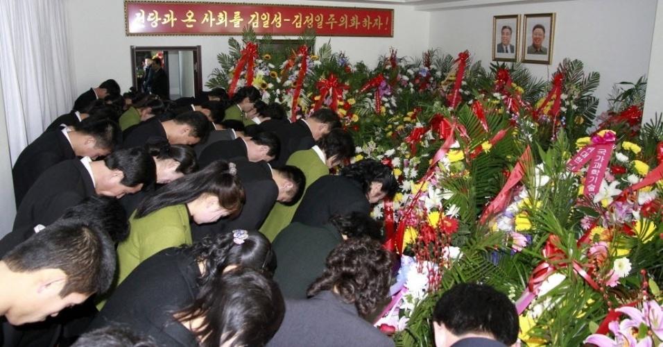 """17.dez.2013 - Norte-coreanos se curvam diante de retratos de Kim Il-sung e Kim Jong-il na embaixada norte-coreana na cidade fronteiriça chinesa de Dandong. Os eventos em homenagem ao segundo aniversário da morte do ex-líder da Coreia do Norte, Kim Jong-il, começaram nesta terça-feira (17) em Pyongyang, em um ambiente marcado pela recente execução daquele que era considerado o """"número 2"""" do regime"""
