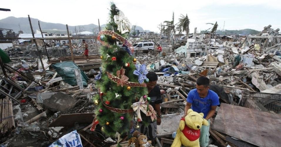 17.dez.2013 - Sobrevivente do tufão Haiyan decora uma árvore de Natal em meio a escombros de casas destruídas na cidade de Tacloban, no centro das Filipinas