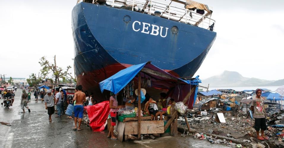 17.dez.2013 - Sobreviventes do tufão Haiyan --que devastou as Filipinas há cerca de um mês-- improvisam  barraca embaixo de navio que foi arrastado para terra, em Tacloban