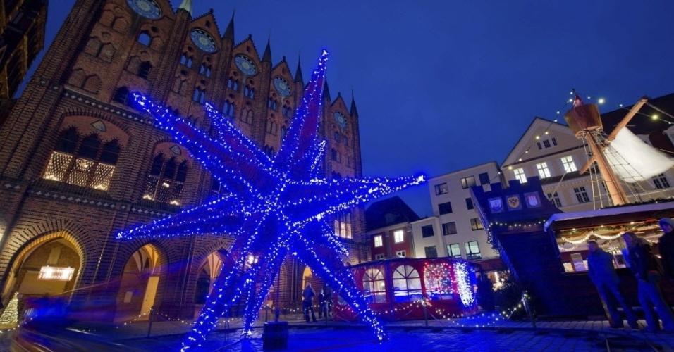 17.dez.2013 - Uma estrela de sete metros de altura, feita de fibra de vidro, ilumina a praça de Stralsund, Alemanha. A estrela feita a mão é uma tentativa de entrar para o livro dos recordes