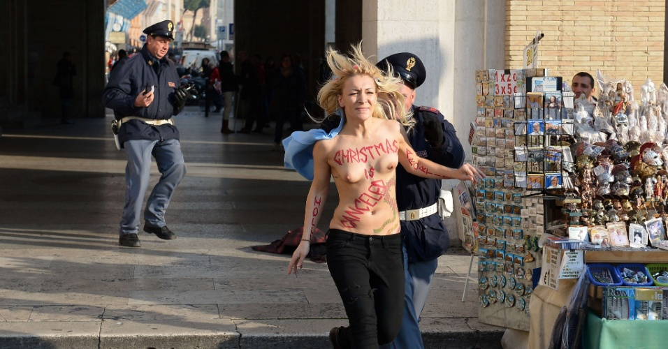 19.dez.2013 - A líder do grupo feminista Femen, Inna Shevchenko, tenta fugir de policial durante protesto a favor do aborto realizado na praça de São Pedro, no Vaticano. Com os seis a mostra, a ativista escreveu no corpo