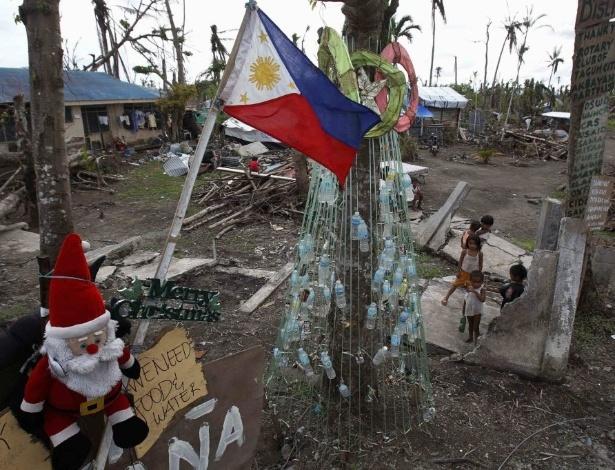 19.dez.2013 - Crianças sobreviventes do tufão Haiyan --que devastou as Filipinas há cerca de um mês-- brincam perto da árvore de Natal improvisada com latas e garrafas vazias na cidade de Tanuan nesta quinta-feira (19). Segundo estimativas oficiais, mais de 6.000 pessoas morreram e 4 milhões estão desabrigadas
