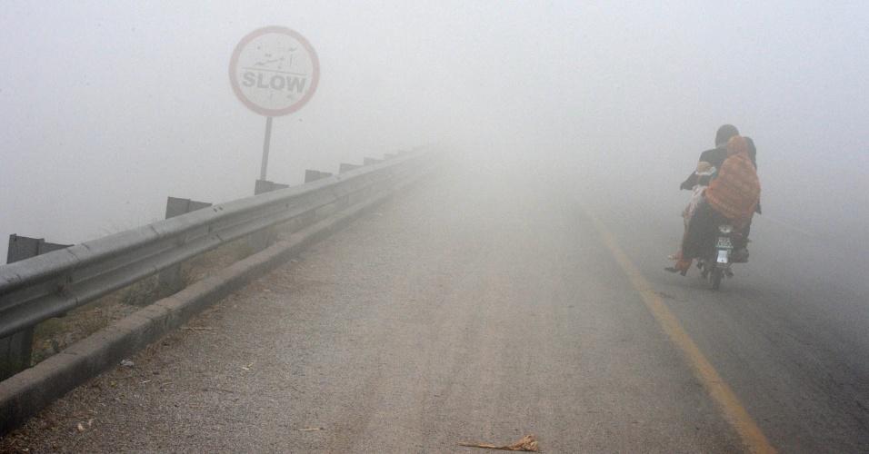 19.dez.2013 - Família paquistanesa enfrenta neblina ao andar de moto por uma estrada de Peshawar, no Paquistão