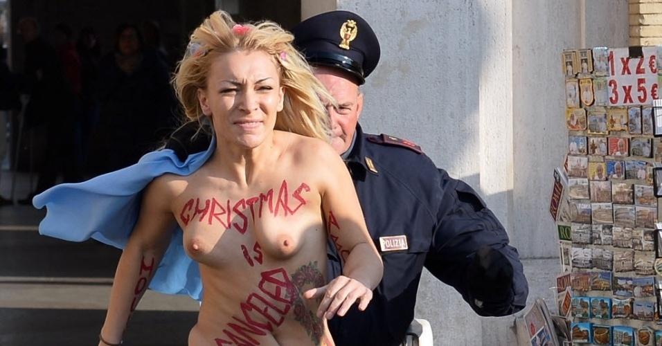 """19.dez.2013 - Inna Shevchenko, líder do grupo feminista Femen, é perseguida por um policial fora praça de São Pedro, no Vaticano. Inna expôs os seios com a frase """"Christmas is canceled, Jesus is aborted"""" (O Natal está cancelado, Jesus foi abortado)"""