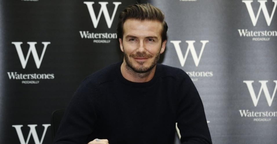 19.dez.2013 - Jogador de futebol aposentado David Beckham posa com livro que leva seu nome em uma livraria de Londres, Inglaterra