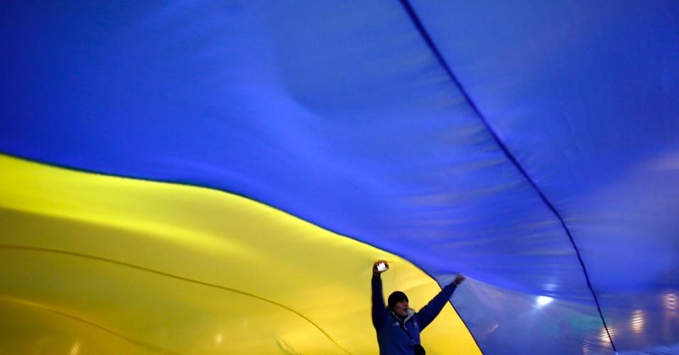 19.dez.2013 - Manifestante a favor da integração da Ucrânia com a União Europeia dança embaixo de uma bandeira nacional gigante na praça da Independência, em Kiev, nesta quinta-feira (19)