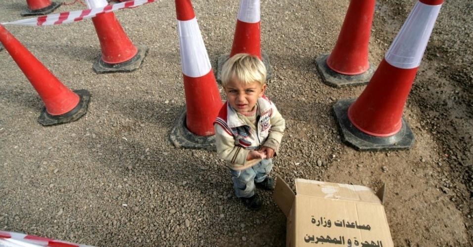 19.dez.2013 - Menino sírio espera na fila para receber alimentos em um campo de refugiados de Quru Gusik, na periferia de Arbil, na região do Curdistão do Iraque. Quase 14 mil sírios curdos vivem na região por conta do conflito civil na Síria