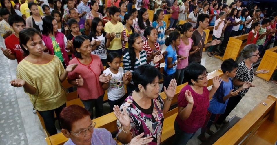 """19.dez.2013 - Sobreviventes do tufão que atingiu as Filipinas em novembro oram durante o quarto dia de uma massa de vigília de Natal, conhecida localmente como """"Misa de Gallo"""" em uma igreja na cidade de Tacloban, no centro do arquipélago"""
