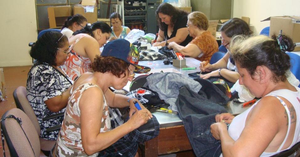 Artesãs recortam logotipos de produtos falsificados pela Receita Federal do Rio Grande do Sul para fazer a descaracterização da mercadorias