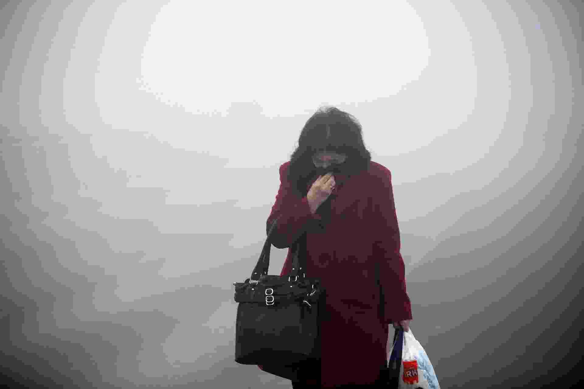 20.dez.2013 - Uma mulher caminha em meio a uma fumaça densa que encobre a cidade de Kakanj, na Bósnia. A fumaça é causada pela mistura da neblina com a poluição industrial, do trânsito e dos incêndios - Dado Ruvic/Reuters