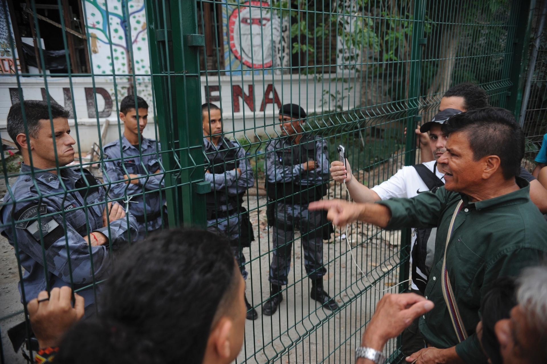 23.dez.2013 - Policiais fazem a segurança do antigo Museu do Índio, no Rio de Janeiro, enquanto índios tentam retomar a posse do local de onde foram expulsos no último dia 16
