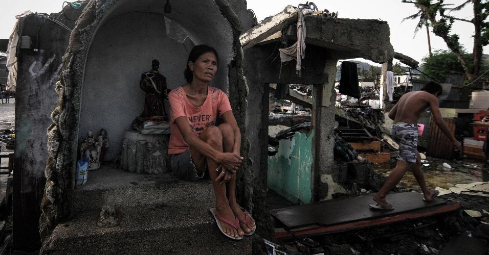 24.dez.2013 - Sobrevivente do tufão Haiyan --que devastou as Filipinas há quase dois meses-- permanece sentada junto a altar danificado em rua de Tacloban --região mais afetada