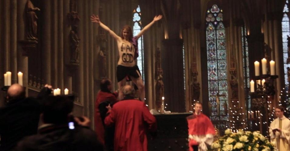 26.dez.2013 - Ativista do Femen fica de topless dentro da catedral de Colônia, na Alemanha. Josephine Witt, 20, saltou sobre o altar, gritou lemas contra a posição contrária do Vaticano em relação ao aborto e exibiu pintura no corpo que dizia