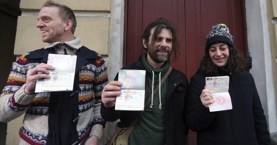 26.dez.2013 - Os ativistas do Greenpeace Mannes Ubels, Ian Rogers e Gizem Akhan (da esquerda para direita) mostram seus passaportes em frente ao Centro de Serviços de Imigração, em São Petersburgo, na Rússia, após terem recebido da Justiça a retirada das acusações contra eles. Agora, eles podem voltar para seus países de origem