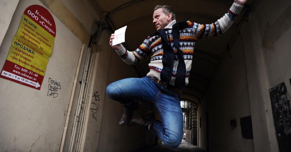 26.dez.2013- Ativista holandês do Greenpeace Mannes Ubels pula ao receber seu passaporte com um visto de trânsito russo, que o permite deixar o país após as acusações contra os 30 manifestantes terem sido retiradas, em São Petersburgo, na Rússia