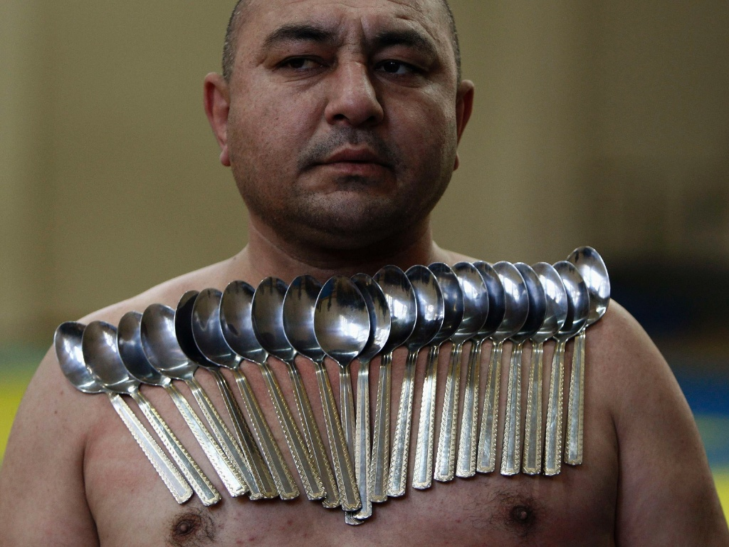 28.dez.2013 - Etibar Elchiyev posa com 53 colheres de metal magnetizadas em seu corpo em tentativa de bater recorde de maior número de colheres presas ao corpo, neste sábado, em Tbilisi, na Geórgia. Elchiyev tenta bater o seu próprio recorde, que é de 50 colheres presas ao corpo