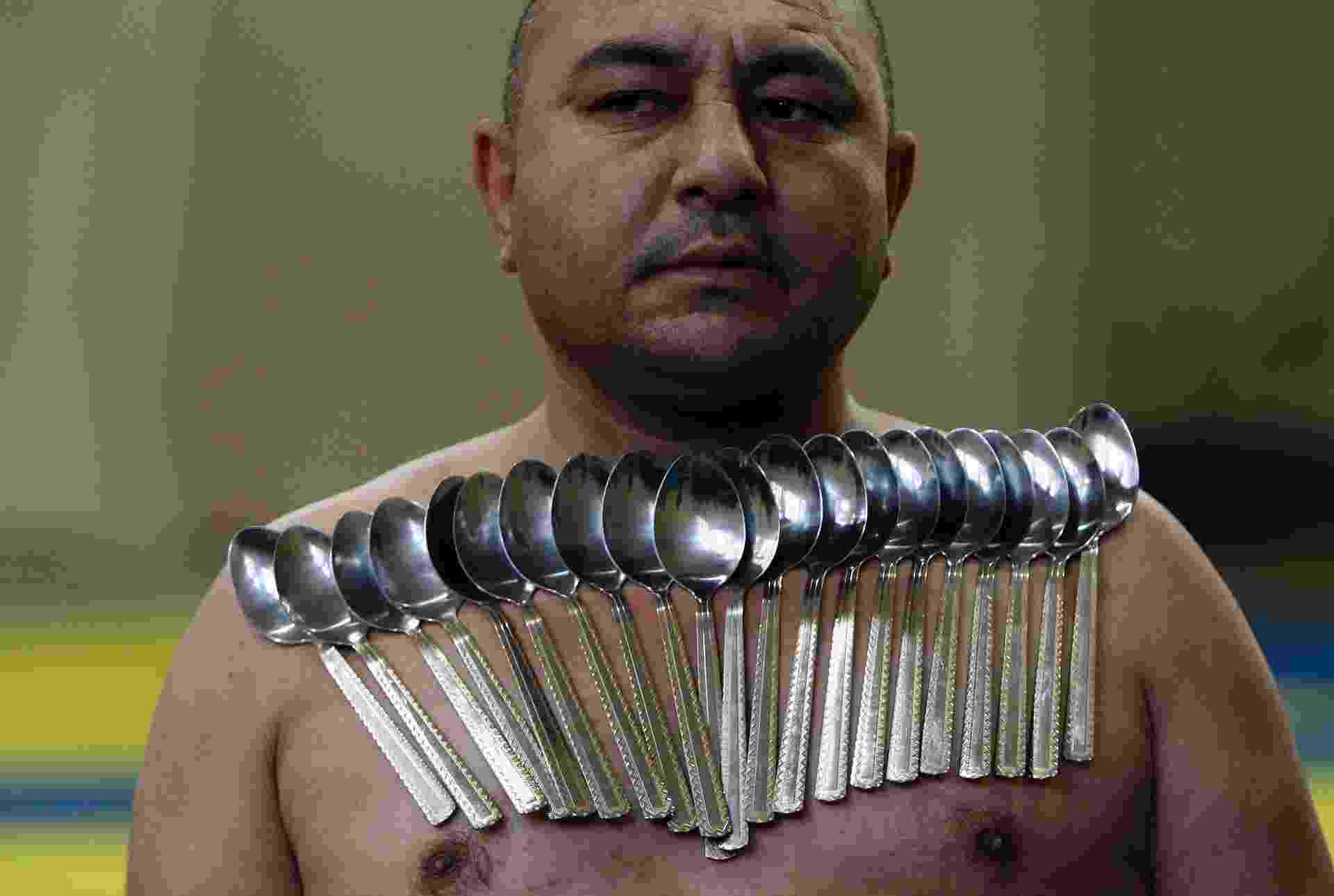28.dez.2013 - Etibar Elchiyev posa com 53 colheres de metal magnetizadas em seu corpo em tentativa de bater recorde de maior número de colheres presas ao corpo, neste sábado, em Tbilisi, na Geórgia. Elchiyev tenta bater o seu próprio recorde, que é de 50 colheres presas ao corpo - David Mdzinarishvili/ Reuters