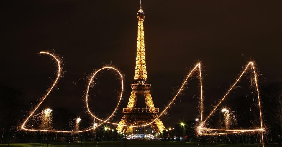 30.dez.2013 - Dois mil e quatorze é escrito no ar com estrelinhas (tipo de fogo de artifício) em frente à Torre Eiffel, antes de chegada do Ano-Novo, em Paris, nesta segunda-feira (30)