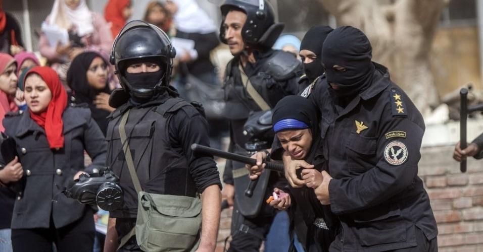 30.dez.2013 - Policial egípcio detém uma estudante da Universidade de al-Azhar, durante um protesto em apoio a a Irmandade Muçulmana, no Cairo, Egito. Uma nova lei de protestos, aprovada neste mês, exige que se peça licença ao Ministério do Interior para protestar