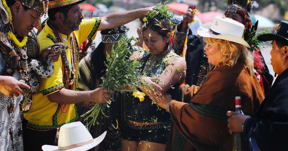 30.dez.2013 - Uma mulher recebe um banho de pétalas de flores de xamãs durante um ritual em que eles são previsões de como será o próximo ano, na praia de Agua Dulce, no Peru, nesta segunda-feira (30)