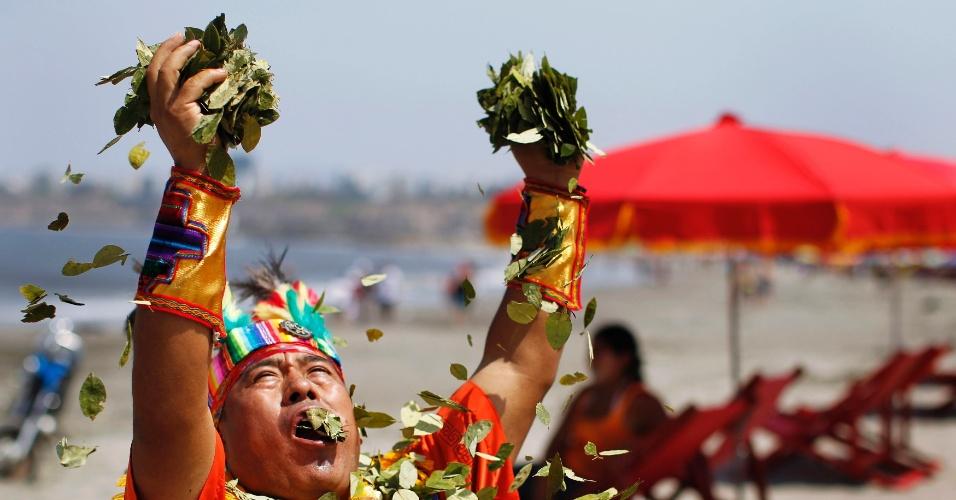 30.dez.2013 - Xamã segura cachos de folhas de coca enquanto participa de cerimônia de previsões para 2014, na praia de Agua Dulce, no Peru, nesta segunda-feira (30)