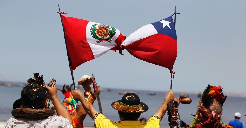 30.dez.2013 - Xamãs amarram bandeiras do Chile e do Peru durante ritual de previsões para 2014, na praia de Agua Dulce, no Peru, nesta segunda-feira (30)