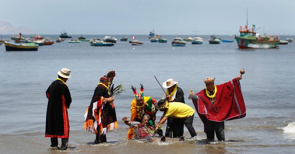30.dez.2013 - Xamãs fazem ritual com um homem, enquanto oferecem previsões para 2014, na praia de Agua Dulce, no Peru, nesta segunda-feira (30)