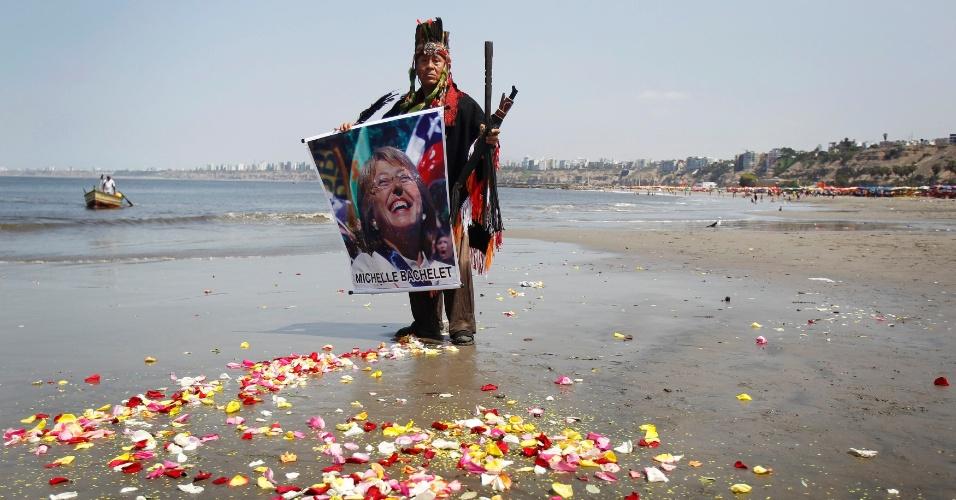 30.dez.2013 - Xamãs seguram cartaz com a foto da presidente chilena eleita, Michelle Bachelet, durante durante ritual de previsões para 2014, na praia de Agua Dulce, no Peru, nesta segunda-feira (30)