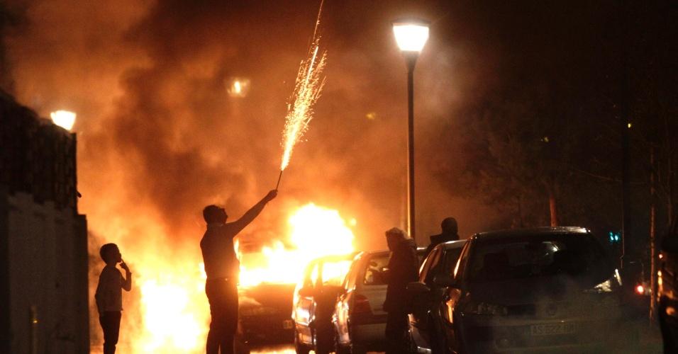 1º.jan.2014 - Homem lança fogos de artifício ao lado de carro em chamas durante as celebrações de Ano Novo em Estrasburgo, na França