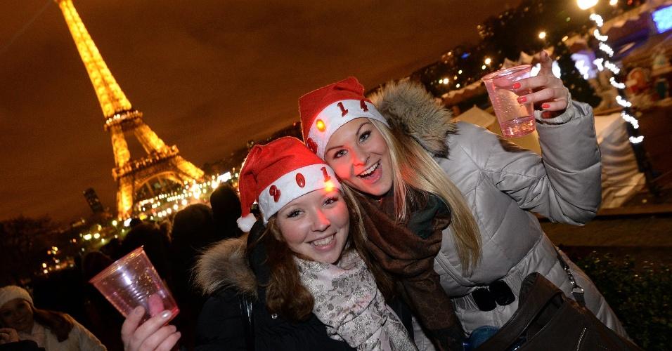 31.dez.2013 - Garotas celebram a passagem do Ano Novo na praça Trocadero, diante da torre Eiffel, em Paris