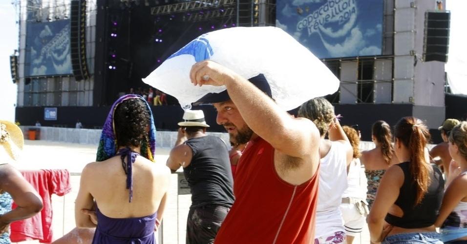 31.dez.2013 - Homem carrega saco com gelo durante preparativos para a festa de Réveillon na praia de Copacabana, na zona sul do Rio, na tarde desta terça-feira (31), para a festa da passagem de ano