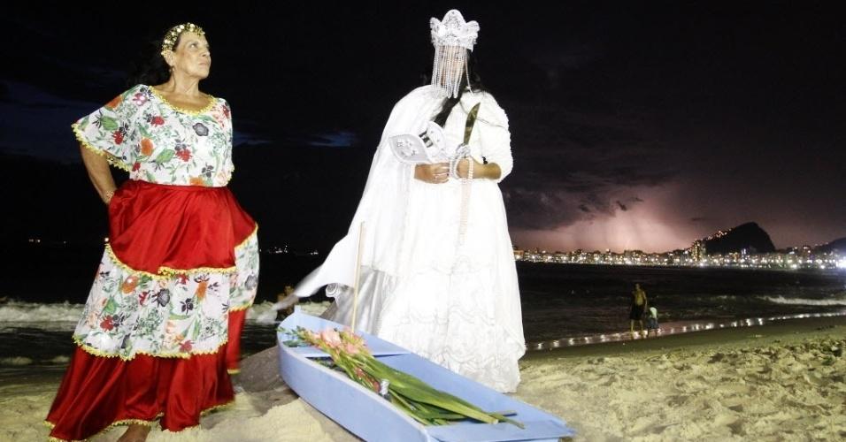 31.dez.2013 - Mulheres entregam oferendas para Iemanjá horas antes da virada do ano, na praia de Copacabana, na zona sul do Rio de Janeiro, durante celebrações da chegada do novo ano