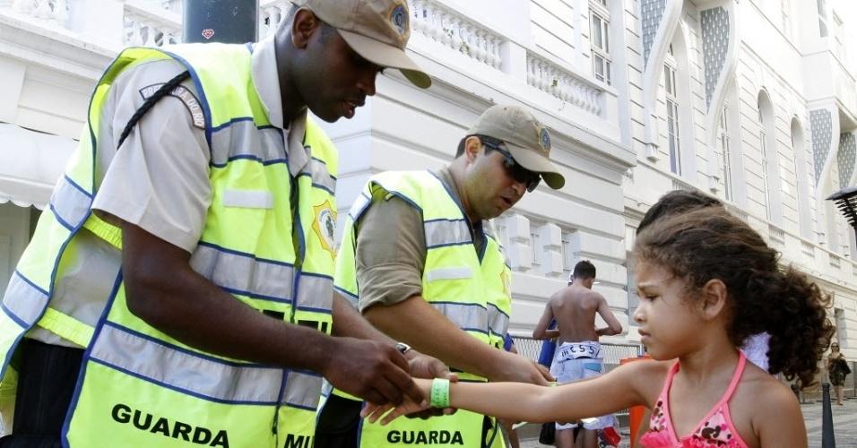 31.dez.2013 - Policiais militares colocam pulseiras de identificação em crianças na praia de Copacabana, na zona sul do Rio, na tarde desta terça-feira (31), para a festa da passagem de ano