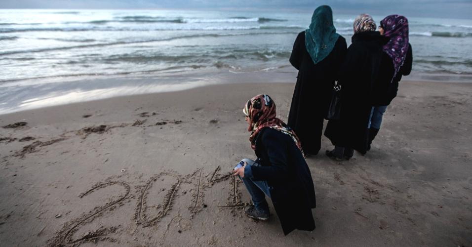 31.dez.2013 - Uma mulher palestina escreve o número 2014 na areia durante celebração da chegada do Ano-Novo, no último entardecer de 2013, na cidade de Gaza