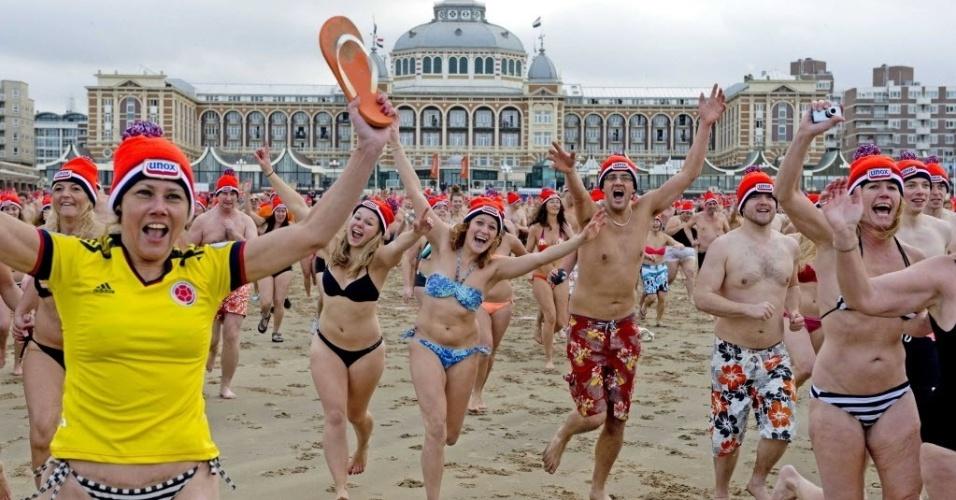 1º.jan.2014 - Com gorros na cabeça, banhistas correm para o tradicional banho de ano novo em Scheveningen, Holanda
